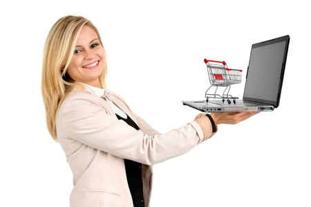 woman shopping cart: Woman with shopping cart and laptop computer isolated in white Stock Photo