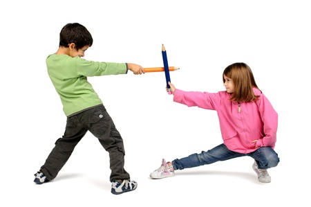 Children couple playing with large pencils isolated in white photo