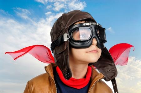 soñando: Piloto muchacho joven contra un cielo nublado azul Foto de archivo