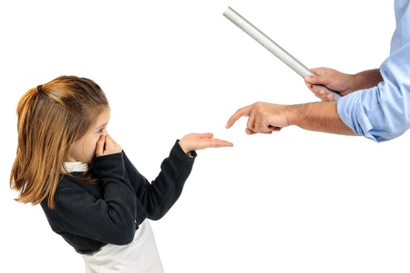 Young girl being physically punished by teacher with a ruler Banco de Imagens