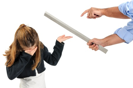 punishments: Young girl being physically punished by teacher with a ruler Stock Photo