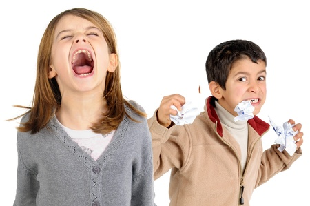 beautiful angry: Young girl screaming and boy chewing paper isolated in white