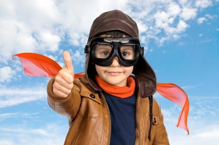flight helmet: Young boy pilotagainst a cloudy sky
