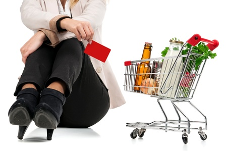 Woman with shopping cart and credit card isolated in white photo