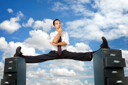 Businessman doing splits over cabinet files Stock Photo - 17537709