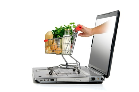 grocery basket: Hand pushing a small shopping cart from  laptop screen isolated in white