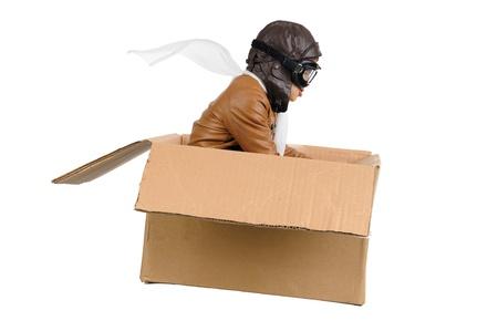 piloto: Chico joven piloto vuela una caja de cart�n aislada en blanco