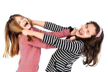 combattimenti: Giovani ragazze lottano, tirando i capelli isolato in bianco