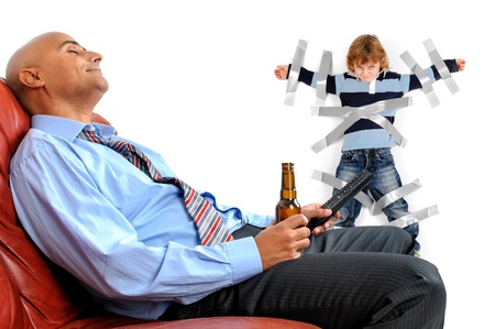 Young boy glued to the wall with duct tape, so daddy can relax and have a beer photo