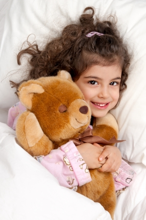 small girl: Beautiful young girl in bed with teddy bear Stock Photo
