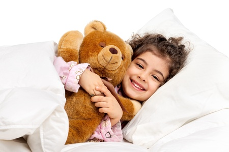 Beautiful young girl in bed with teddy bear Banco de Imagens - 17926653