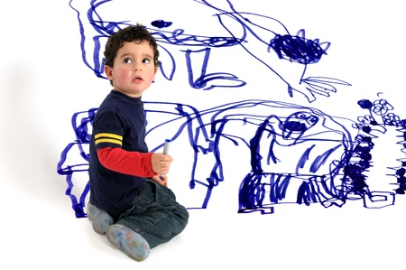 messy kids: Young artistic boy doing wall painting Stock Photo