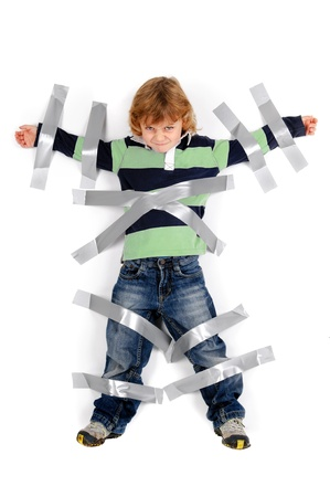 Young angry boy glued to the wall with duct tape