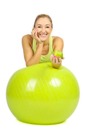 light diet: woman with pilates ball and an apple isolated in white Stock Photo