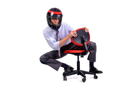 Businessman racing in a chair with helmet Stockfoto