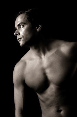 Handsome and muscular man in dark background photo