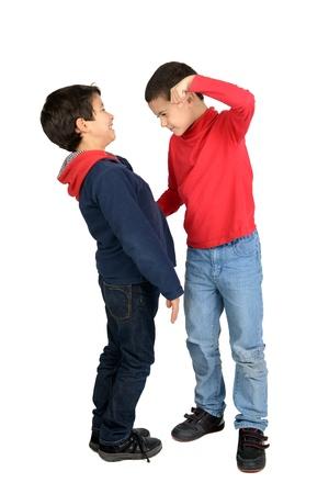 ni�os malos: Boy intimidaci�n a un ni�o peque�o aislado en blanco Foto de archivo