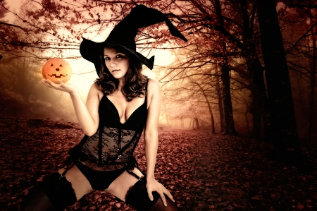 broom: Sexy  girl in witch costume for Halloween in a forest
