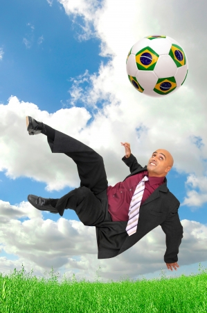 Businessman in a acrobatic pose kicking a soccer ball in a green field photo