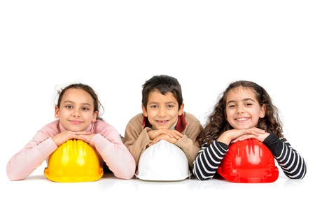 protective helmets: Group of children posing with protective helmets isolated in white