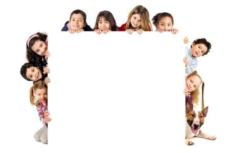 Gruppe von Kindern und ein Hund mit einem weißen Brett isoliert in weiß