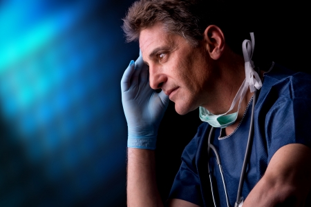 Tired doctor in uniform isolated against a black background photo