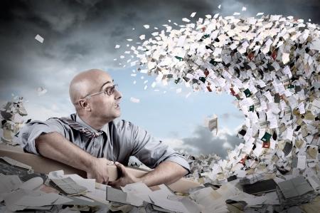 Castaway Geschäftsmann in einem Meer von Papieren und Dateien