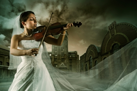 Beautiful bride playing the violin photo
