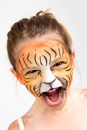 Beautiful young girl with face painted like a tiger Stockfoto