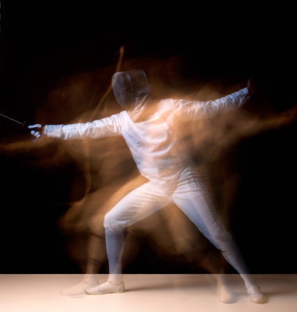 thrust: Male fencer isolated in a dark background Stock Photo