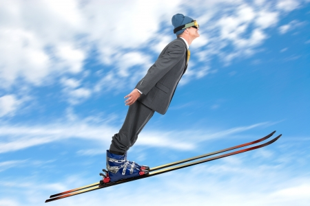 Businessman ski jumping against the sky