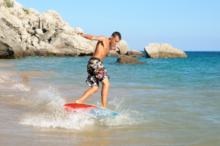 skimming: Teenager surfing in the beach