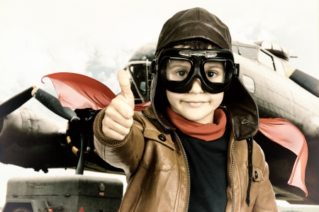 Young boy pilot iposing with big bomber in the background photo