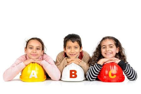 protective helmets: Gruppo di bambini in posa con caschi di protezione isolato in bianco