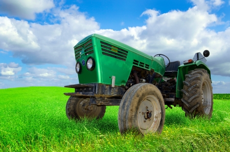 Green tractor in the field with a cloudy sky Stock Photo - 22028137