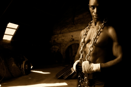 Beautiful and muscular black man with chains in dark background photo