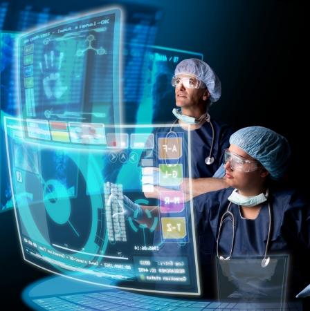 Artsen in een onderzoeksstation met digitale schermen en toetsenbord Stockfoto