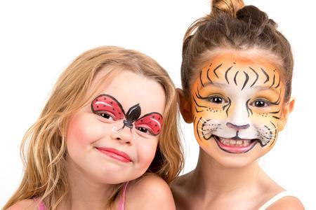 Schöne junge Mädchen mit bemalten Gesichtern, Tiger und Marienkäfer