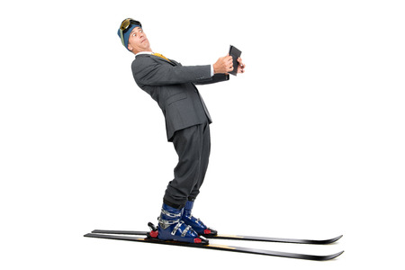 Businessman with ski gear and tablet isolated in white photo