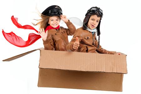 karton: Fiatal fiú pilóta és lány repül egy kartondobozban elszigetelt fehér Stock fotó