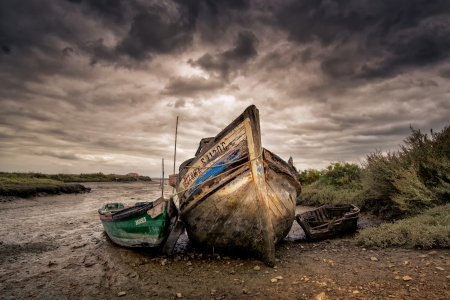 Old fishing boats abandoned in a dry river bed photo