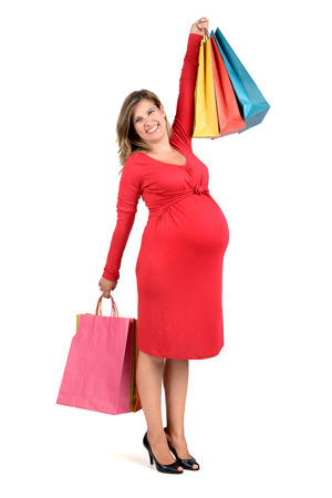 Beautiful pregnant woman posing in red dress with shopping bags Stock Photo