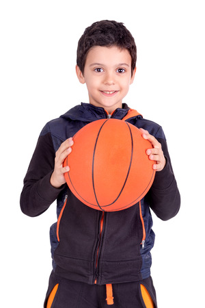 Young boy posing with a basketball ball isolated in white photo