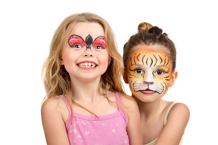kids painting: Beautiful young girls with painted faces, tiger and ladybug