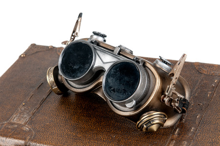 015a9bcf9dc Steampunk goggles over a suitcase isolated in white Stock Photo