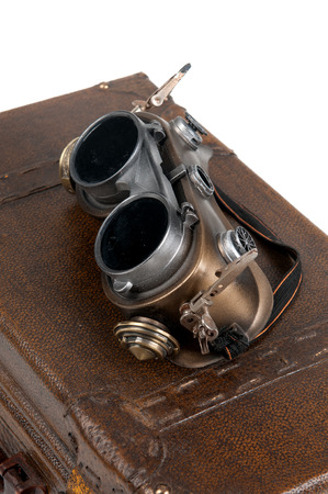 ww2: Steampunk goggles over a suitcase isolated in white Stock Photo