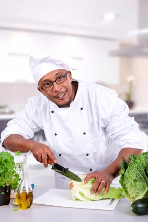 Male chef with fruits and vegetables on table photo