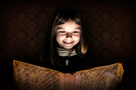 Young girl reading a very old book isolated in black