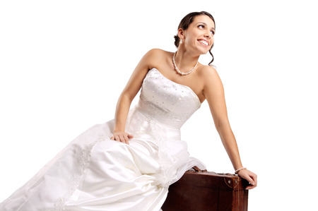Beautiful bride posing with an old suitcase isolated in white photo