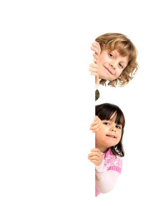 Kinderen die met een wit bord geïsoleerd in het wit Stockfoto - 26117189